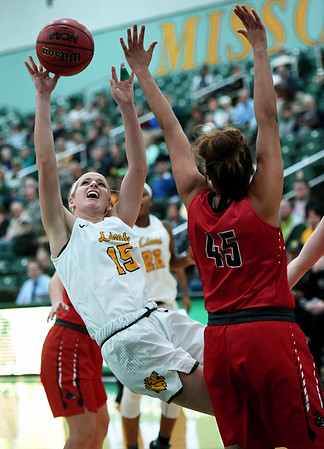 Missouri Southern's Chelsey Henry (15) puts up an off-balance shot as Central Missouri's Kim Crown (45) defends during their game on Thursday night at Leggett & Platt.<br /> Globe | Laurie Sisk