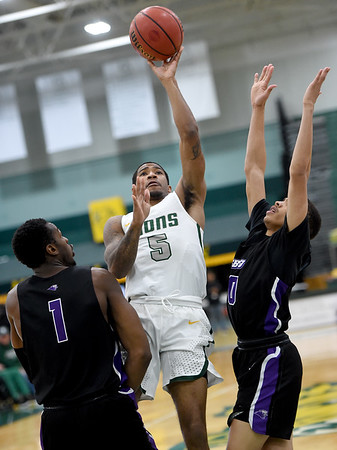 Missouri Southern's Braelon Walker (5) shoots as Southwest Baptist's Karim Mouliom (1) Chris Rossow (0) defend during their game on Saturday at Leggett & Platt.<br /> Globe | Laurie Sisk