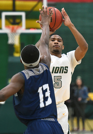 Missouri Southern's Braelon Walker (5) scores over Washburn's Tyas Martin (13) during their game on Wednesday night at Leggett & Platt.<br /> Globe | Laurie Sisk
