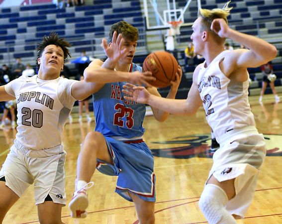 Joplin's Isaiah Davis (20) and Blake Tash (12) try to stop Webb City's Austin Bash (23) during their third place game in the Kaminsky Classic on Saturday at Joplin High School.<br /> Globe | Laurie Sisk