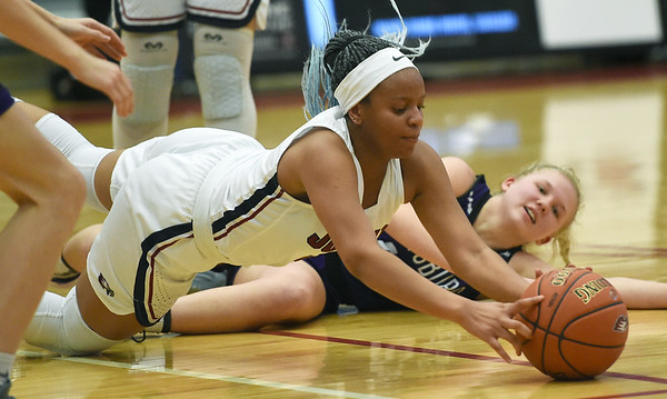 From the left: Joplin's Avery Gage (5) and Pittsburg's Madden Petty (12) dive for a loose ball during their game on Tuesday night at Kaminsky Gymnasium.<br /> Globe | Laurie Sisk