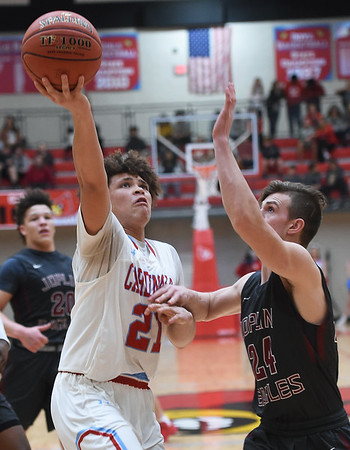 Webb City's Nickhai Howard (21) drives and scores on Joplin's Alex Crawford (24) during their game on Tuesday night at Webb City High School.<br /> Globe | Laurie Sisk