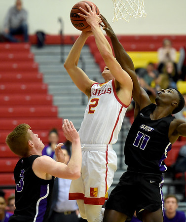 Pittsburg State's Grant Lozoya (2) draws a foul on Southwest Baptist's Tyler Williams (11) as Quinn Nelson (3) looks on during their game on Wednesday night at John Lance Arena.<br /> Globe | Laurie Sisk