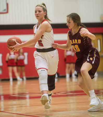 Carl Junction's Dani Wrensch makes a pass under pressure from Girard's Bailey Troike during Monday's game in Carl Junction.<br /> Globe | Roger Nomer