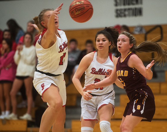 Carl Junction's Shila Winder (12) and Jessa Hylton (21) make a steal from Girard's Makaila Ausemes during Monday's game in Carl Junction.<br /> Globe | Roger Nomer