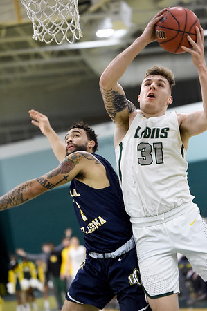 Missouri Southern's Cam Martin (31) drives to the basket as Central Oklahoma's Dashawn McDowell (3) defends during their game on Thursday night at Leggett & Platt.<br /> Globe | Laurie Sisk