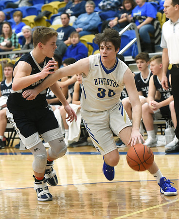 Riverton's Carter Brown (30) works to get past Galena's Garrett Lawson (15) during their game on Friday night at RHS.<br /> Globe   Laurie Sisk