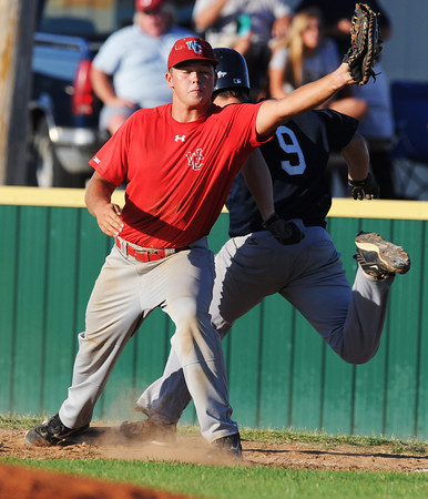 Globe/Roger Nomer<br /> Webb City's (31) hangs on for the force out of Joplin's (9) at first during the first game on Thursday at Barnes Field.