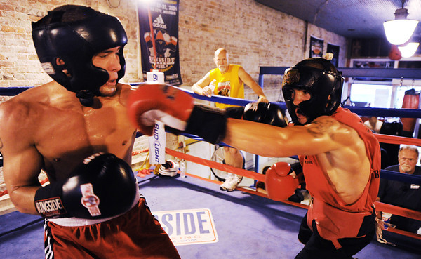 """Globe/T. Rob Brown<br /> Jesse """"Left Hook"""" Cook (left) and brother Dillon """"White Lightning"""" Cook, both of Seneca, spar during training at Heartland Boxing Gym in downtown Galena, Kan., recently. Their father, head trainer Dallas Cook, looks on."""