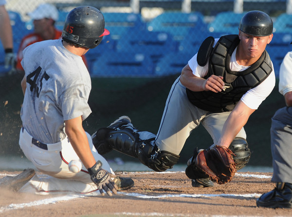 Globe/Roger Nomer<br /> Houston Kyle Chapman's Bryce Packard beats the throw home to Midwest Nationals Cole Sanderson to score the team's first run of the game in the first inning during pool play at the Premier Baseball Tournament at Joe Becker Stadium on Wednesday.