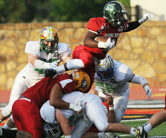 Globe/Roger Nomer<br /> East's Ra'Keim Abdul, Shawnee Mission South High School, leaps over the West's defense during the first quarter of the Kansas Shrine Bowl at Pittsburg State University's Carnie Smith Stadium in Pittsburg, Kan., on Saturday, July 26, 2014.