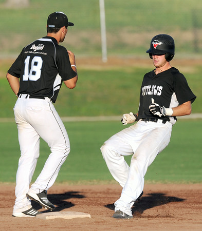 Outlaws infielder Matthew Turner makes it easily to second after a Sedalia throwing error to first base during  Joplin's game against the Bombers  on Thursday night at Joe Becker Stadium. Also pictured is Sedalia's XXXX XXX (18).<br /> Globe | Laurie Sisk
