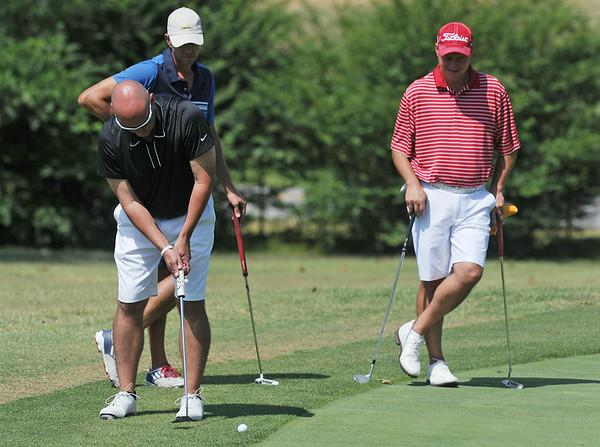 Globe/Roger Nomer<br /> Chris Patterson hits onto the green as Todd Doss, middle, and Andy Pochik stand by during Friday's Twin Hills Invitational.