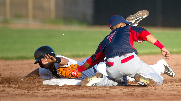 Joplin's Sergio Leon reaches for the bag but is tagged out by Lincoln's Dainer Moreira on a steal attempt during the Blasters' game against the Saltdogs on Thursday night at Joe Becker Stadium.<br /> Globe | Laurie Sisk