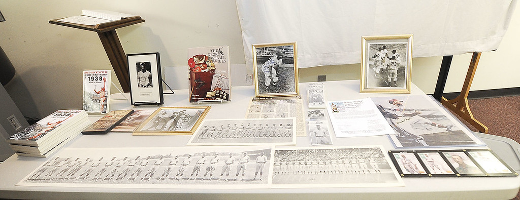 Memorbilia and books from and about the Negro Leagues grace a table at the Joplin Public Library on Thursday during a presentation by author and Negro Leagues Museum co-founder Phil S. Dixon. Globe   Laurie Sisk