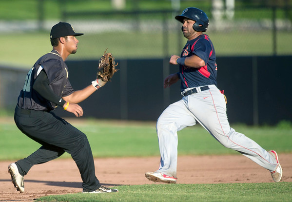 Lincoln's Luis Alen runs past Joplin's Alex Poston during the Blasters' game against the Saltdogs on Friday night at Joe Becker Stadium.<br /> Globe | Laurie Sisk