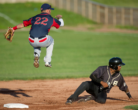 Lincoln'c Tyler Urps leaps to avoid a sliding Geraldo Valentin during the Blasters' game against the Saltdogs on Friday night at Joe Becker Stadium.<br /> Globe | Laurie Sisk