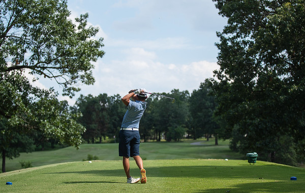 Jordan Burks tees off No. 16 as he keeps an eye on his shot  during the final round of the Joplin Area Golf Championships at Briarbrook Golf Course in Carl Junction.<br /> Globe|Israel Perez