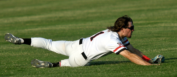 Oulaws centerfielder Alec Capshaw hangs onto the ball after a diving catch during Joplin's game against the Jefferson City Renegades on Tuesday night at Joe Becker Stadium.<br /> Globe   Laurie Sisk