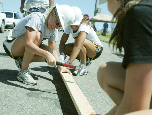 Globe/Roger Nomer<br /> Kim Lambert, associate athletic director for student-athlete development, left, and Katelyn Trevino, gymnast, hammer a board while working on a Habitat house on Friday.