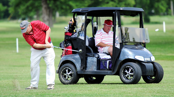 Globe/T. Rob Brown<br /> Gary Maham drives the ball from the fairway Saturday afternoon, June 9, 2012, as Rusty Smith, both of Carl Junction, sits in the duo's cart at Briarbrook Golf Course and Country Club.