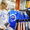 Globe/T. Rob Brown Kyle Tastad, 16, of South Dakota, who is in Joplin on a mission trip to help Joplin rebuild, looks at the Oklahoma City Thunder T-shirts for sale at TNT Sports at Northpark Mall in Joplin.