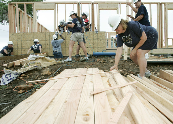 Globe/Roger Nomer<br /> Lisa Grace, an executive assitant travel coordinator with the St. Louis Rams, works with lumber at a house on 2322 Pennsylvania on Thursday.