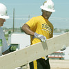Globe/Roger Nomer<br /> Volunteer Wayne Schwickerath, Ames, Iowa, hands University of Missouri quarterback James Franklin a board while working on a house on Pennsylvania on Friday.