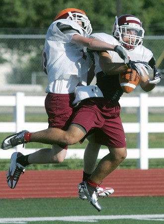 Globe/Roger Nomer<br /> Johnathon Wenthe knocks a pass away from Justice Westerman during Joplin High's summer football camp on Wednesday.