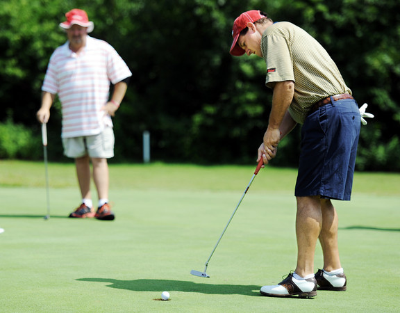 Globe/T. Rob Brown<br /> Andy Pochik sinks a putt Saturday afternoon, June 9, 2012, as Rusty Smith, both of Carl Junction, looks on at Briarbrook Golf Course and Country Club.