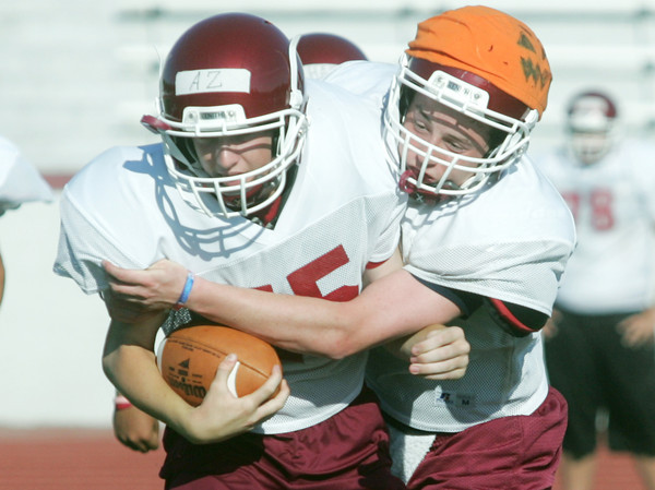Globe/Roger Nomer<br /> Lane Freeborn wraps ups Austin Zengel during Joplin High's summer football camp on Wednesday.