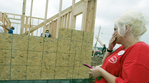Globe/Roger Nomer<br /> Tracy Anderson holds back tears as she watches the walls go up on her new house at 2322 Pennsylvania on Thursday.