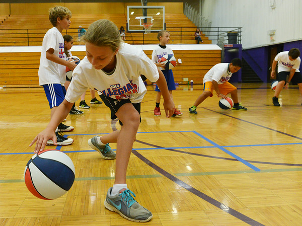 Globe/Roger Nomer<br /> Caleigh Ratzlaff, 10, practices her dribbling during the Collegiate All-Stars Basketball Camp at Pittsburg High School on Monday.