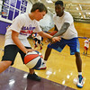 Globe/Roger Nomer<br /> Kansas University's Jamari Traylor gives Drew Cambers, 9, a lesson on how to protect the ball during the Collegiate All-Stars Basketball Camp at Pittsburg High School on Monday.