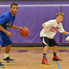 Globe/Roger Nomer<br /> Conner Taylor, 11, gets some help on his dribbling form from Kansas University's Frank Mason during the Collegiate All-Stars Basketball Camp at Pittsburg High School on Monday.