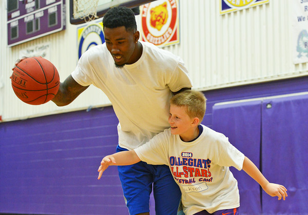 Globe/Roger Nomer<br /> Jackson Turnbull, 9, tries to make a steal from Kansas University's Jamari Traylor during the Collegiate All-Stars Basketball Camp at Pittsburg High School on Monday.
