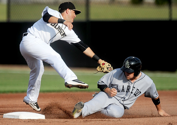 Laredo's J.D. Pulfer slides under the tag of Blasters shortstop Will Soto during their game on Tuesday night at Joe Becker Stadium.<br /> Globe | Laurie Sisk