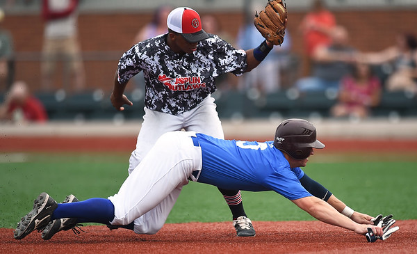 Outlaws shortstop Freilen Cabrera gets the out on diving Playmakers shortstop XX (3) during their game on Saturday night at Joe Becker Stadium.<br /> Globe | Laurie Sisk