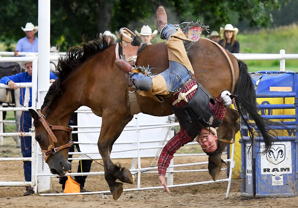 Josh McKee takes a tumble during the saddle bronc competition on Saturday night at the 42nd Annual Carthage Stampede Rodeo at the Carthage Saddle Club Arena.<br /> Globe | Laurie Sisk