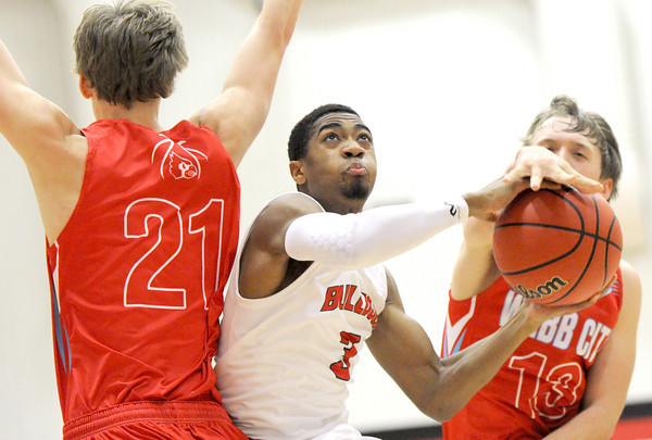 Carl Junction's Matt Magee (3) drives past Webb City's Preston Ellis (21) and Channing Mickey (13) during their Class 4 District 12 semifinal game on Thursday night at Carl Junction.<br /> Globe   Laurie Sisk