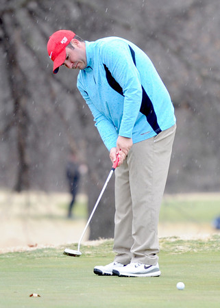 Webb City High School golfer Colton Craig watches his putt roll toward the cup as a cold rain and brisk winds hit the course on Wednesday at Brairbrook Country Club.<br /> Globe | Laurie Sisk