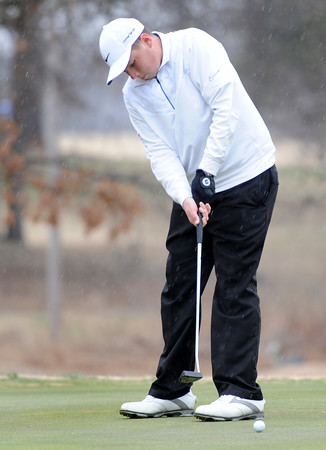 Carthage High School golfer Trent Carson  watches his putt roll toward the cup as a cold rain and brisk winds hit the course on Wednesday at Brairbrook Country Club.<br /> Globe | Laurie Sisk