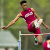 Jopln's Evan Guillory scissors his way over the bar during the Boys' High Jump at the Carthage Invitational on Friday at Carthage's K.E. Baker Stadium.<br /> Globe | Laurie Sisk