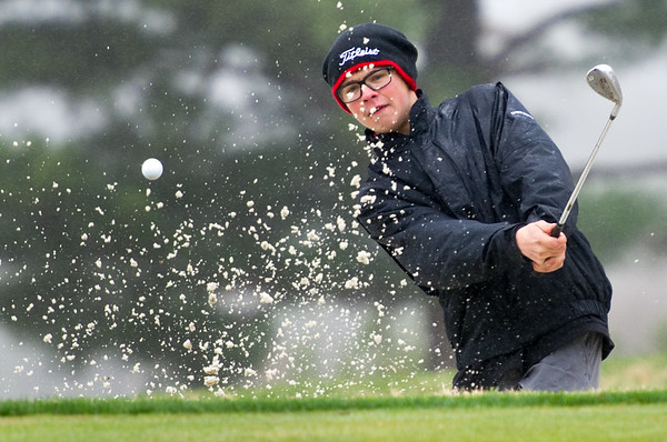 Joplin golfer Taylor Robeson hits a chip shot out of the bunker on a rainy Thursday at Twin Hills.<br /> Globe | Laurie Sisk