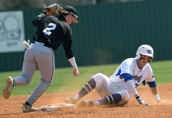 Crowder's Kobe Morris slides into second base a little late as Maple Woods shortstop xx (2) logs the out during their game on Thursday at Crowder.<br /> Globe | Laurie Sisk