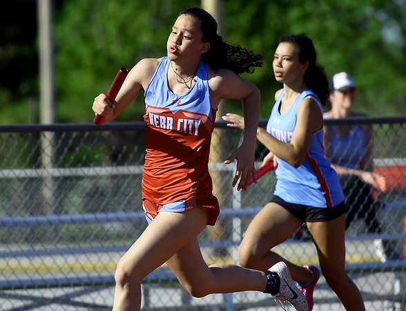 Webb City's Raven Vaughn, left,  passes Glendale's Essence Kibby on the second leg of the 4x200 relay the Webb City Invitational on Friday at WCHS. Webb City placed first in the event. <br /> Globe | Laurie Sisk