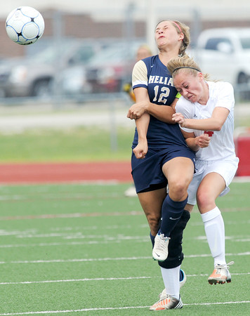 Carl Junction forward Callie Degani (4) and Helias defender Caitlin Luebbert collide after vieing for a header during their state quarterfinal match on Saturday at Carl Junction.<br /> Globe | Laurie Sisk