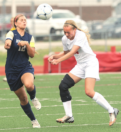 Carl Junction forward Callie Degani (4) and Helias defender Caitlin Luebbert (12) battle for a header during their state quarterfinal match on Saturday at Carl Junction.<br /> Globe | Laurie Sisk