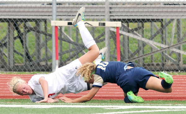 Carl Junction midfielder Lauren Buchele (3) and Helias midfielder Casey Lisenbardt (10) fall to the ground after colliding during their state quarterfinal match on Saturday at Carl Junction.<br /> Globe | Laurie Sisk