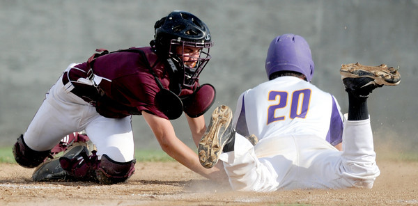 Monett's Jordan Hall slides in safely at home ahead of Rogersville catcher Connor Pomering's tag during their state playoff game on Thursday at Monett.<br /> Globe | Laurie Sisk